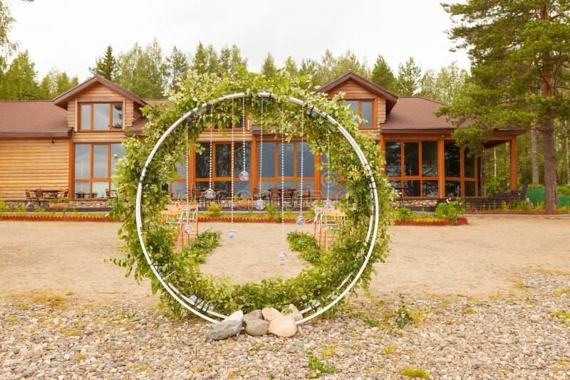 美好的婚姻的设定 婚礼的区域 半圆拱,用花装饰的棕色椅子,绿叶 逗人喜爱,时髦 库存照片
