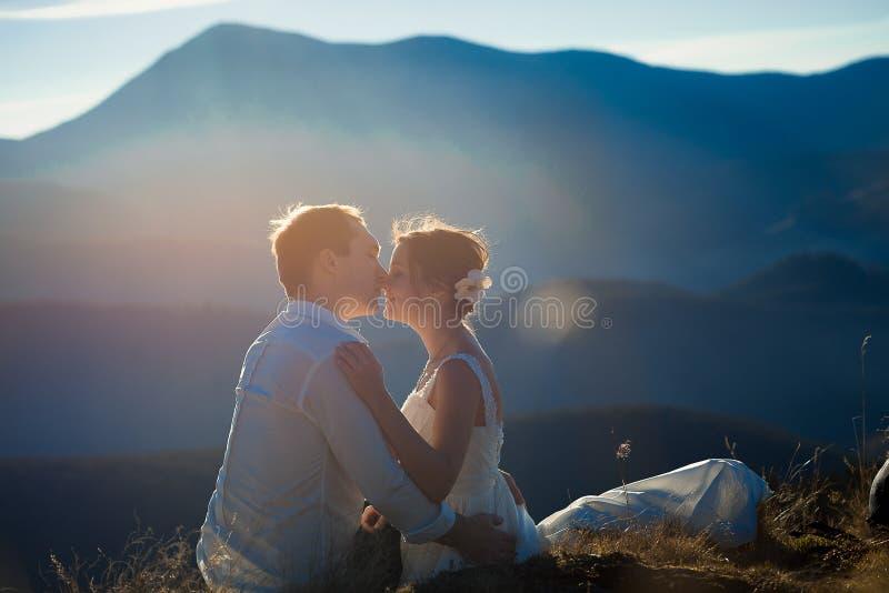 美好的婚礼夫妇软软地亲吻 背景的阿尔卑斯 免版税库存照片