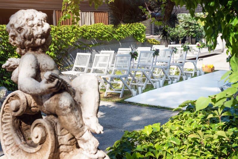 美好的婚礼设定 婚礼在庭院里 用花装饰的白色木椅子,气球和 免版税库存照片