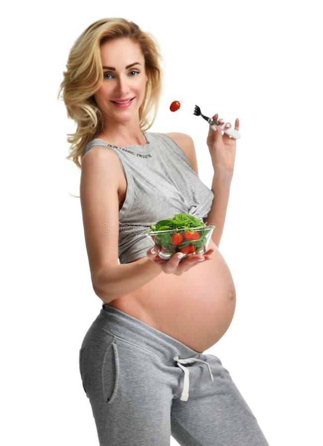 美好的孕妇举行有机沙拉 怀孕母性期望健康吃 免版税库存照片