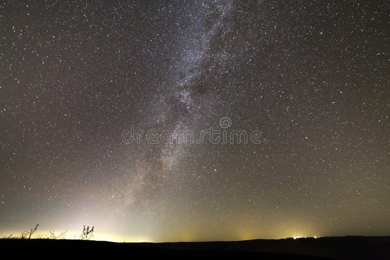 美好的宽全景,农村风景在晚上 与白色闪耀的星,银河星系无数的无边的黑暗的天空和 免版税库存图片