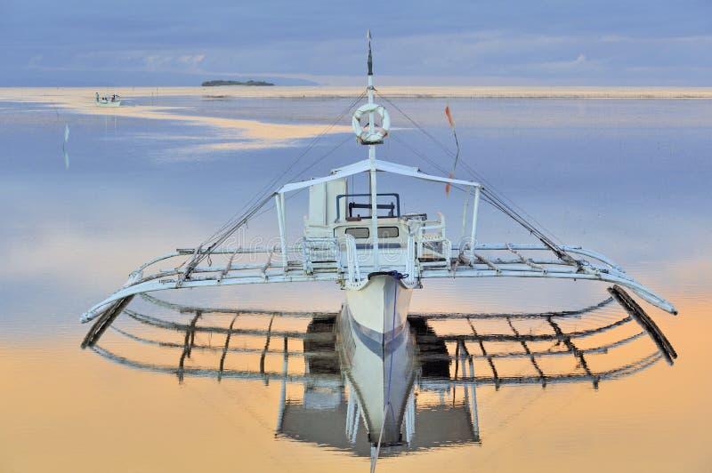美好的小船安静海洋舷外架日出 免版税库存照片