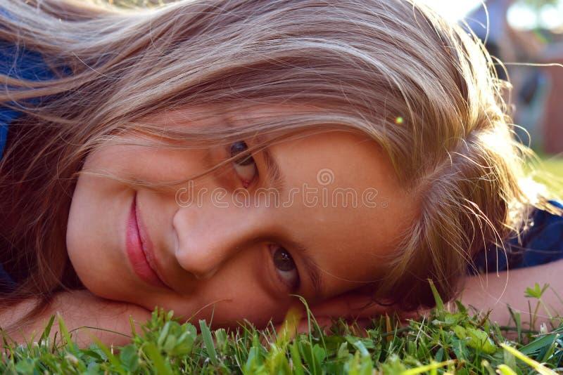 美好的少女关闭在绿草在夏天 女孩的微笑的童颜 免版税库存照片