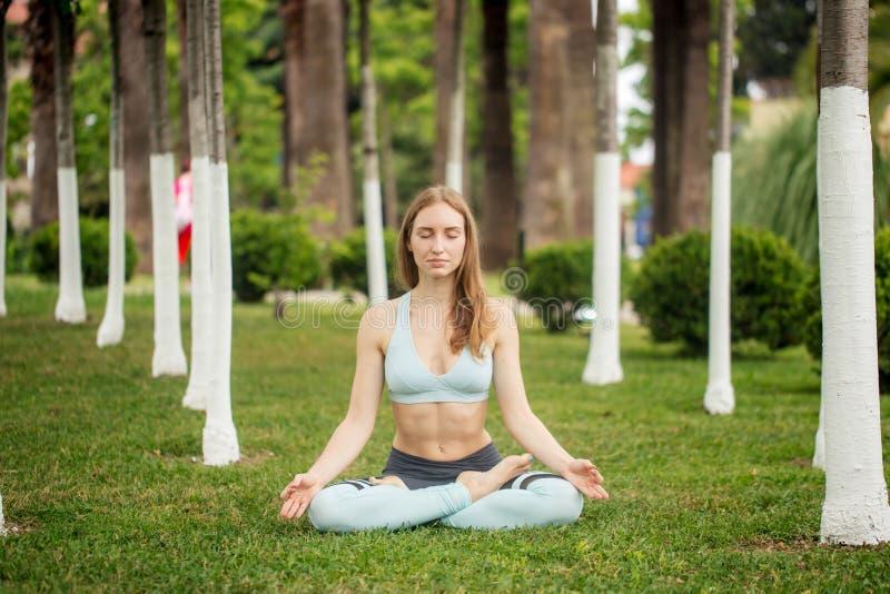 美好的少妇实践的瑜伽在公园和做namaste mudra 免版税图库摄影