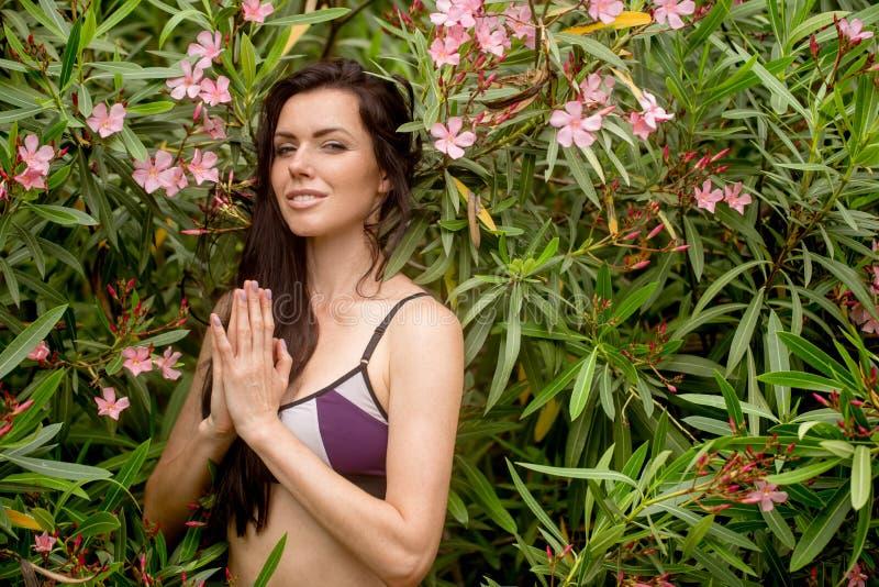 美好的少妇实践的瑜伽在公园和做namaste mudra 免版税库存照片