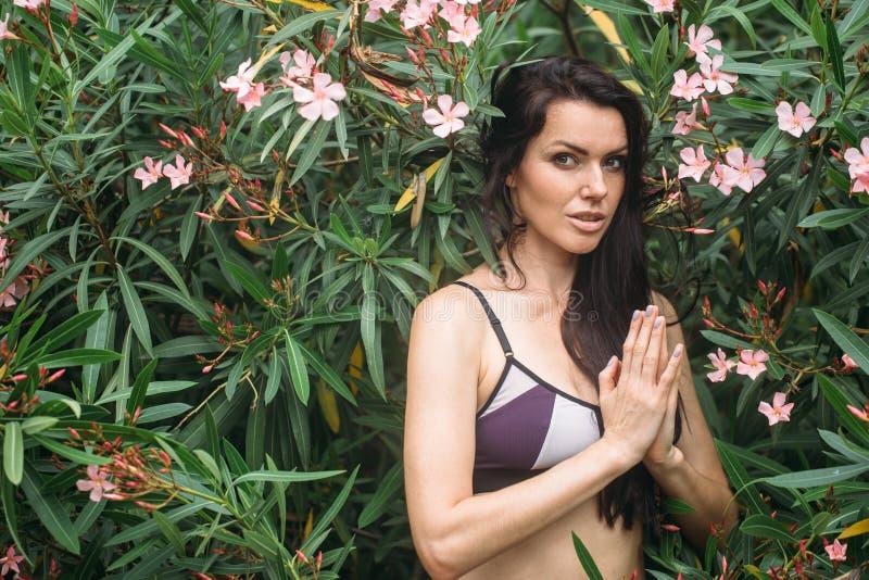美好的少妇实践的瑜伽在公园和做namaste mudra 库存图片