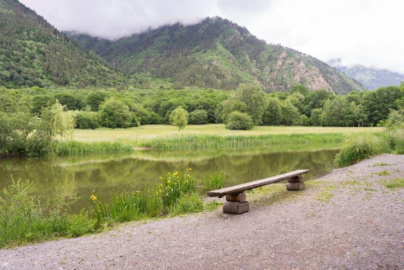 美好的山森林风景 由俯视山的湖的长凳 库存图片