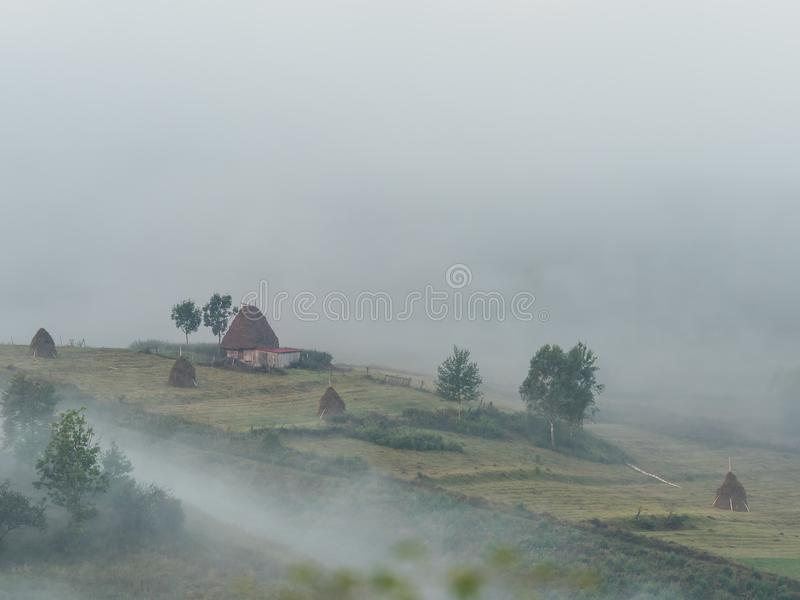 美好的山风景与和老房子、树和干草堆在一个有雾的早晨 图库摄影