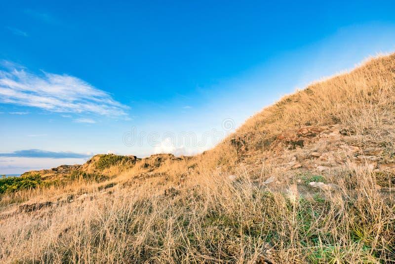美好的岩石山lanscape和干燥草甸蓝天的 免版税库存照片