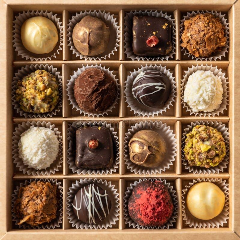 美好的巧克力糖、白色、黑暗和牛奶巧克力的分类在箱子 甜点背景,顶视图 库存图片