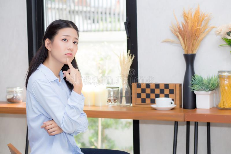 美好的年轻亚洲妇女幸福画象和在咖啡馆商店认为坐 免版税库存照片