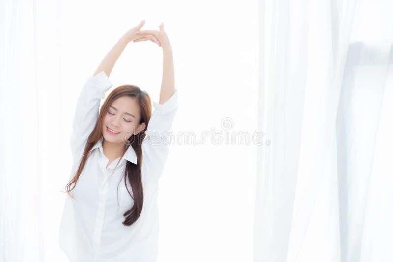 美好的年轻亚洲妇女舒展和在床上放松身分以后在卧室叫醒早晨 图库摄影
