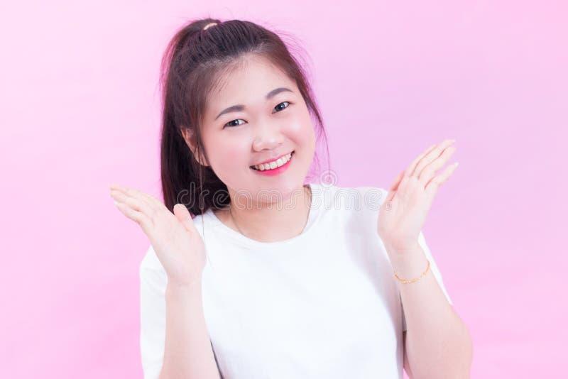 美好的年轻亚洲妇女黑发穿戴画象一件白色T恤杉用开放手 愉快和明亮的感觉 库存图片
