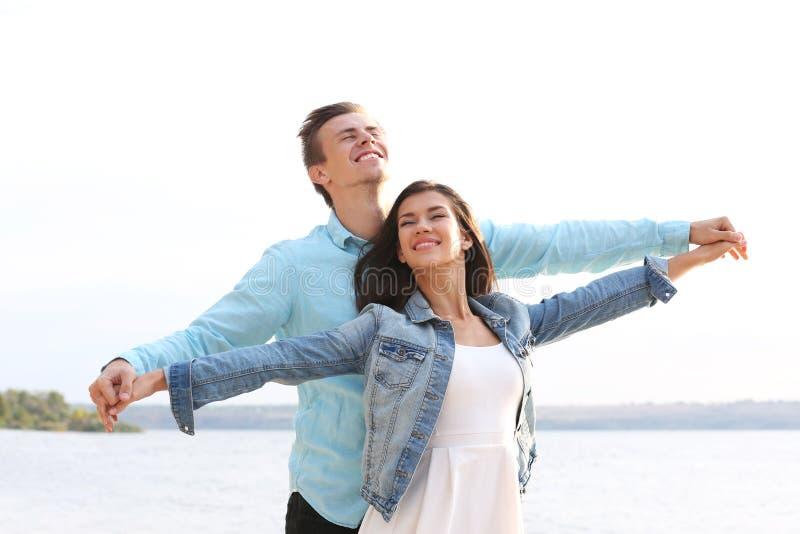 美好的年轻夫妇临近背景的河 免版税库存图片