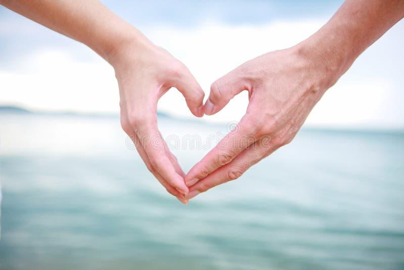 美好的年轻夫妇做与手指的心脏 免版税图库摄影