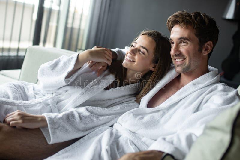 美好的年轻夫妇在卧室在床上说谎 一起享受消费的时间 库存图片