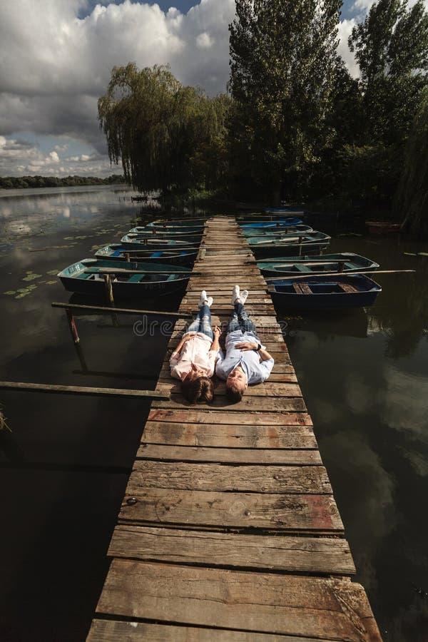 美好的年轻夫妇在湖的一个木桥说谎,爱恋注视着彼此和微笑 r 免版税库存照片