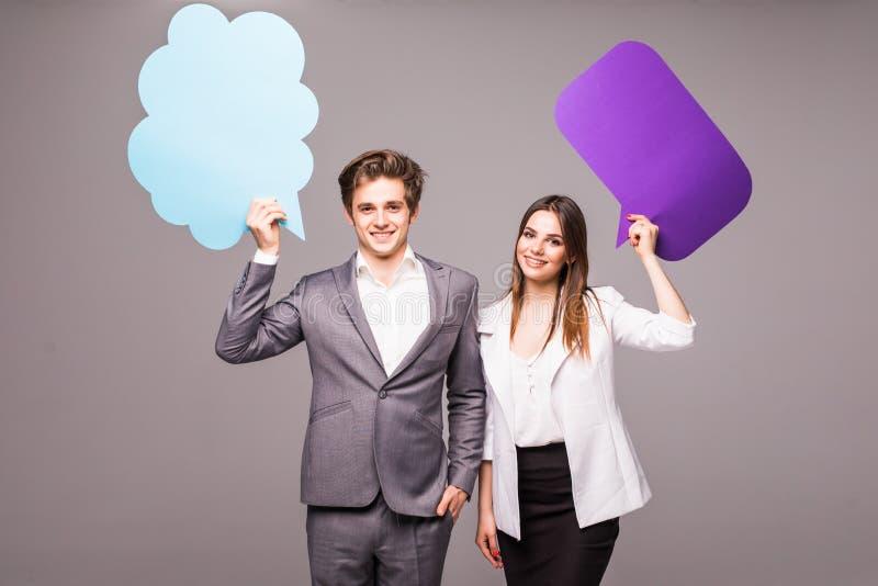 美好的年轻夫妇在灰色拿着讲话泡影,看照相机并且微笑着, 免版税库存照片