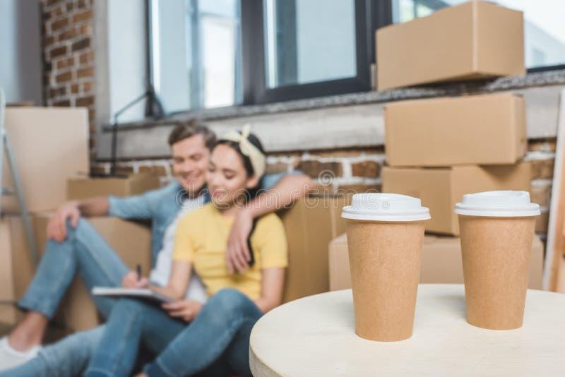 美好的年轻夫妇坐地板,当搬入新的家用咖啡去时 库存图片