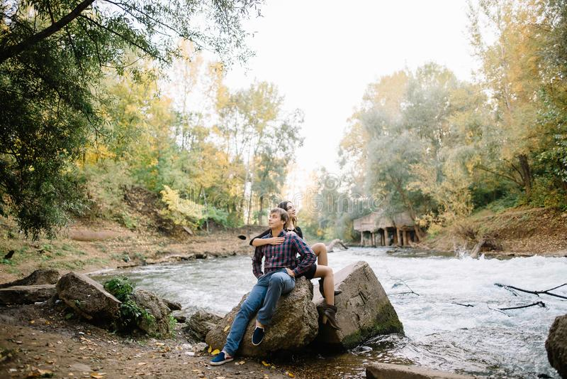 美好的年轻夫妇坐岩石在河附近,本质上 库存图片