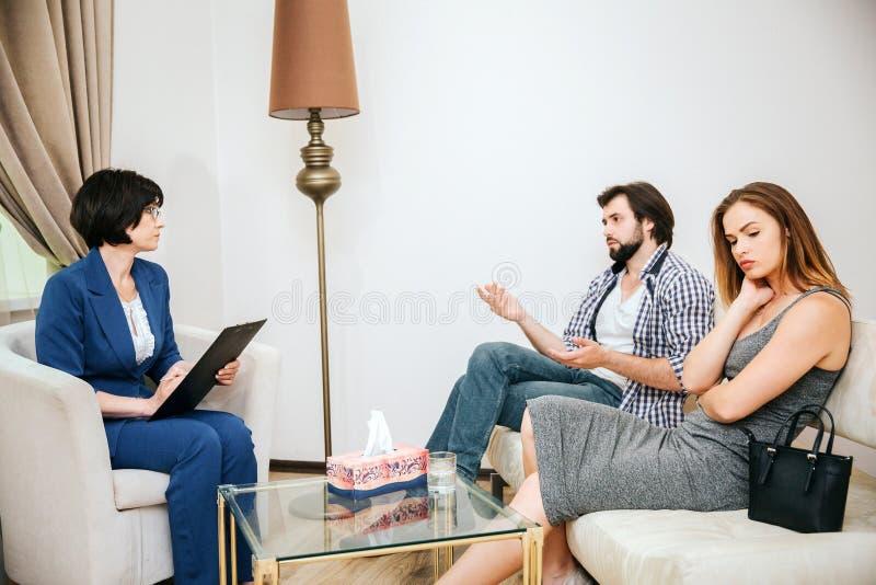美好的年轻夫妇坐沙发 人与医生听他的心理学家谈话 女孩生气 免版税库存图片