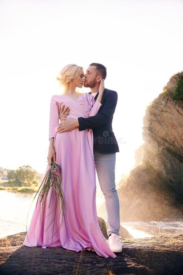美好的年轻夫妇拥抱和看看和享受在河的彼此一个浪漫日期 照相机首先查出人计划常设工作室白人妇女 库存图片