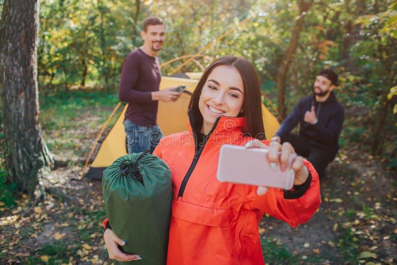 美好的年轻女人作为selfie和微笑的图片 她拿着睡袋 后面姿势的年轻人  他们 免版税库存照片