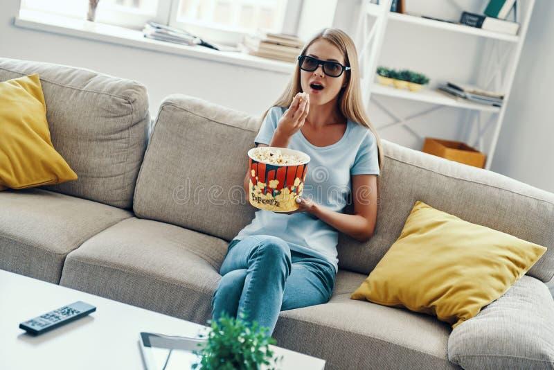 美好的年轻女人看着电视 库存照片