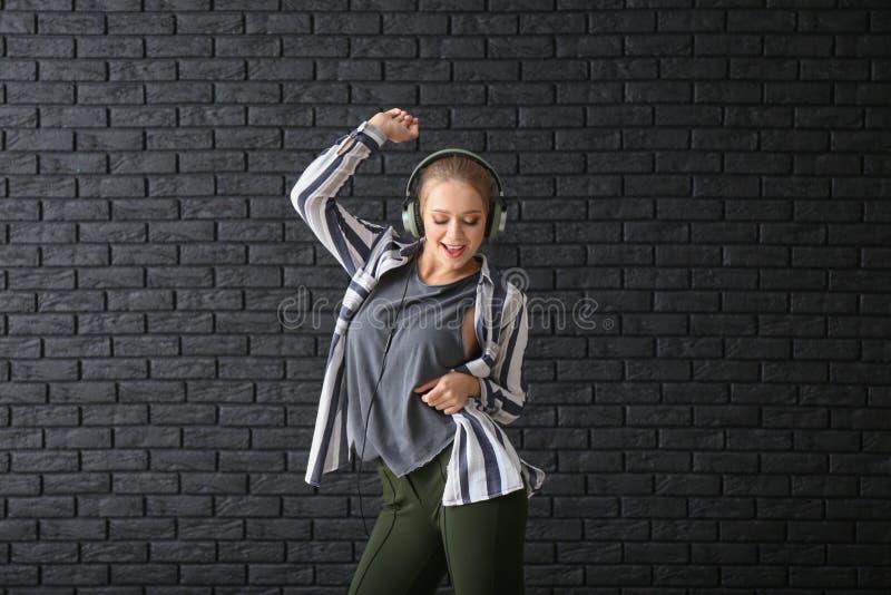 美好的年轻女人跳舞对黑暗的砖墙 免版税库存图片