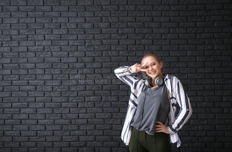 美好的年轻女人跳舞对黑暗的砖墙 免版税图库摄影