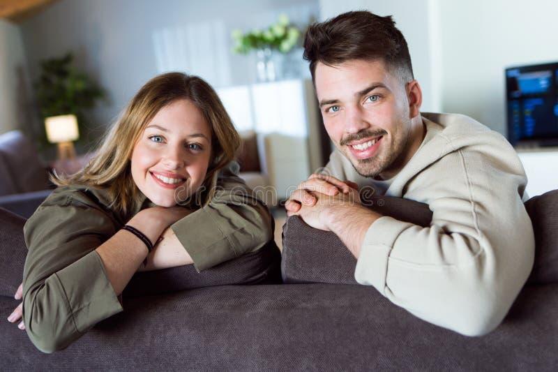美好的年轻微笑的夫妇看照相机和在家坐沙发 图库摄影
