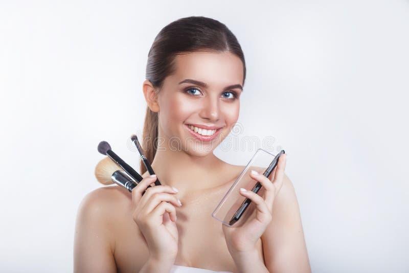 美好的年轻微笑的女性模型和在白色背景的眼影特写镜头与化妆刷子的 免版税库存图片