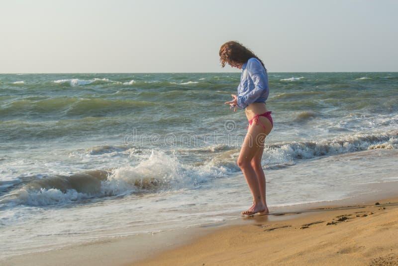 美好的年轻性感的妇女身分在海滩的水中 库存照片