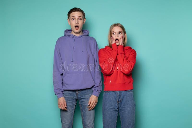美好的年轻惊奇的夫妇画象在便服的,看与开放嘴的照相机 免版税图库摄影