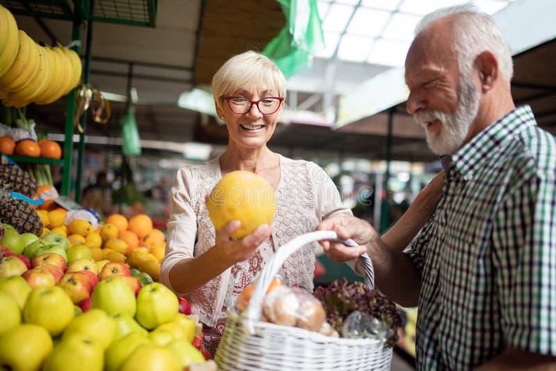 美好的年长夫妇画象在市场buing的食物的 图库摄影