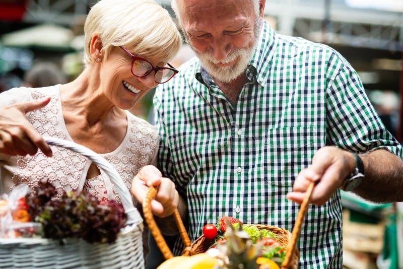美好的年长夫妇画象在市场buing的食物的 免版税库存照片