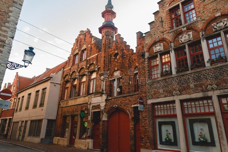 美好的建筑学低角度视图在狭窄的历史街道上的在布鲁基,比利时 库存图片