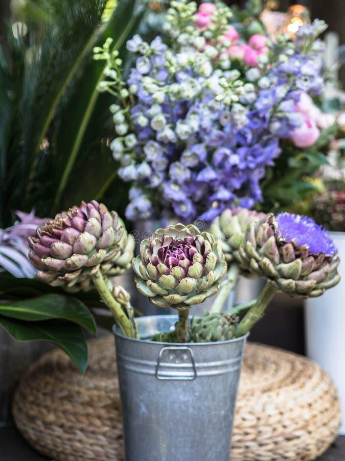 美好的开花的装饰分支用朝鲜蓟在金属桶开花 免版税库存照片