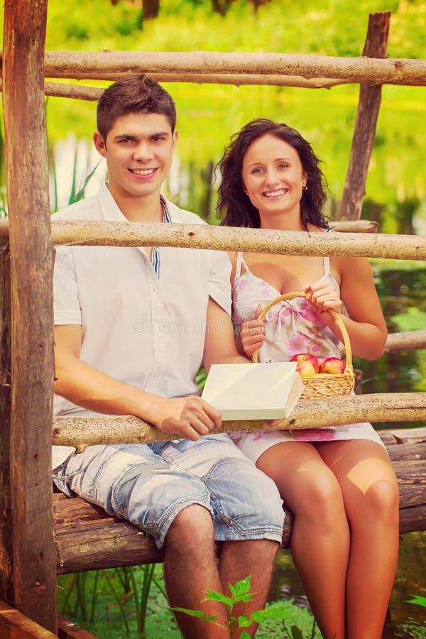 美好的微笑的夫妇坐在小r的老木桥 库存图片