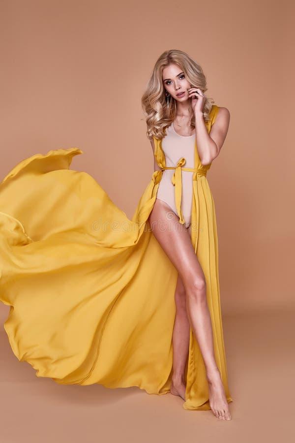 美好的性感的妇女白肤金发的继承人穿戴长的丝绸礼服画象  免版税库存图片