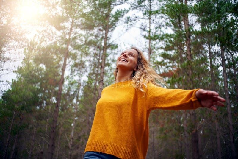 美好的愉快的白肤金发的年轻女人跳舞在森林里 免版税库存图片