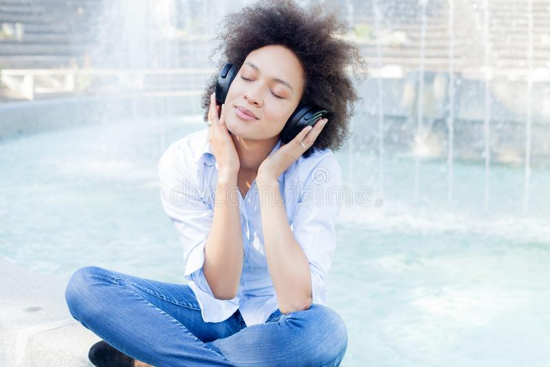 美好的愉快的黑少妇听的音乐 免版税库存图片
