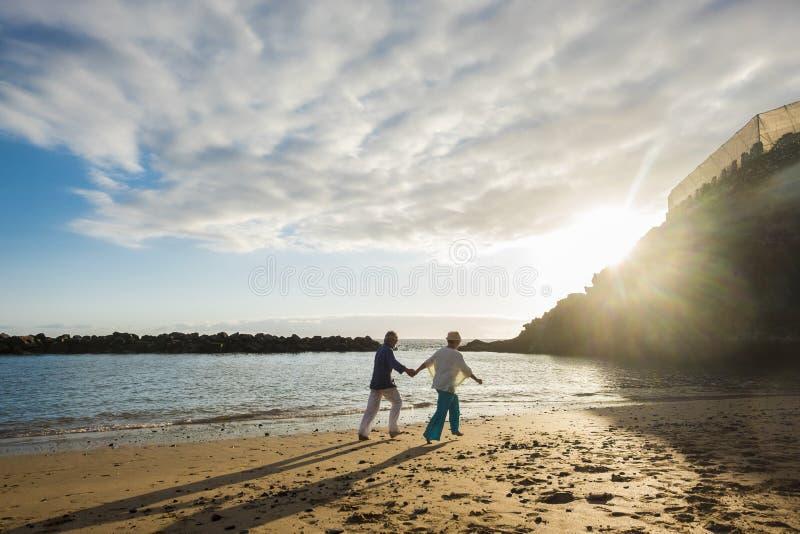 美好的成熟夫妇室外在娱乐活动一起进行在在一起生活的岸的海滩垂悬手和 免版税图库摄影