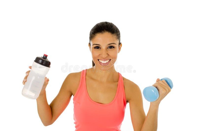 美好的拿着水瓶和手重量的适合拉丁体育妇女 免版税库存照片