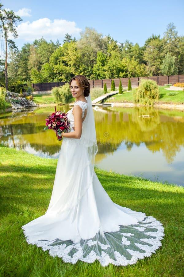 美好的拿着bouque的婚礼白色礼服的可爱的新娘 免版税库存图片