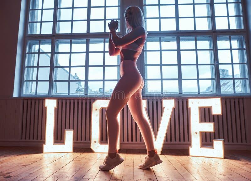 美好的摆在大被阐明的词爱附近的健身模型佩带的运动服在有推力内部的一间屋子里 爱 图库摄影