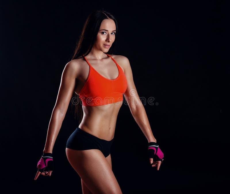 美好的摆在黑背景的activewear的健身性感的亭亭玉立的女性 免版税库存图片