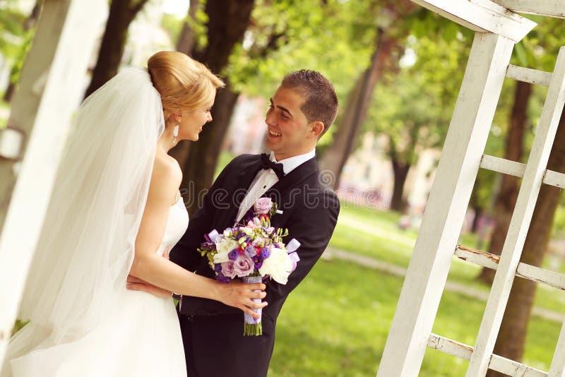 美好的新娘夫妇获得乐趣在他们的婚礼之日花花束的公园 免版税库存照片