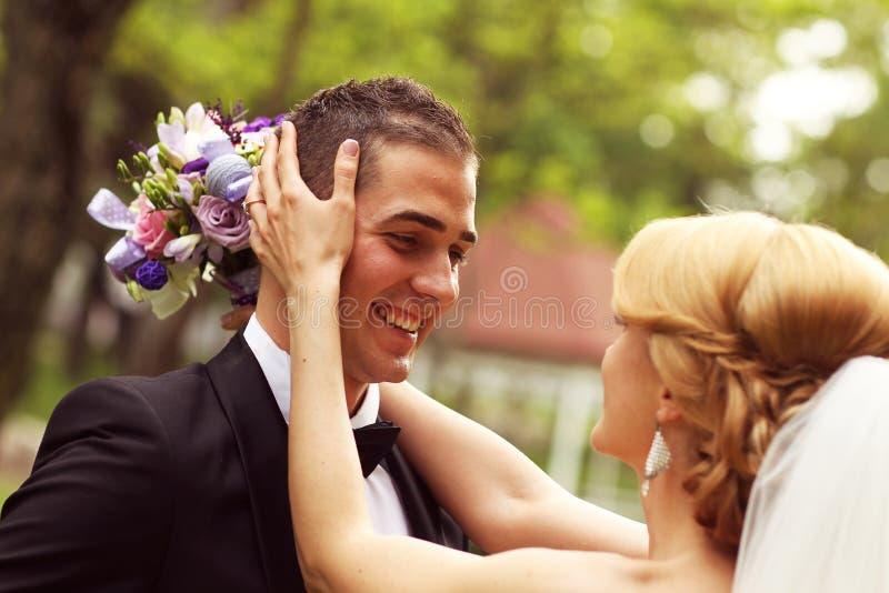 美好的新娘夫妇获得乐趣在他们的婚礼之日花花束的公园 免版税库存图片
