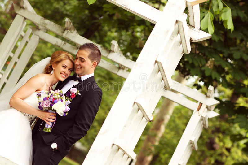 美好的新娘夫妇获得乐趣在他们的婚礼之日花花束的公园 免版税图库摄影